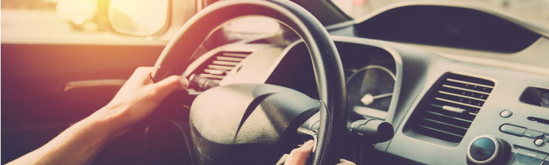 Image of steering wheel and dashboard console focused on drivers side of car with man's hands on steering wheel